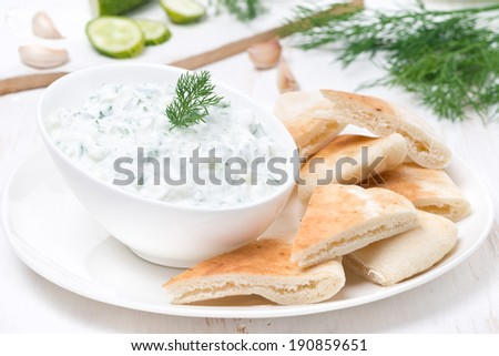 yoghurt sauce tzatziki with pieces of pita bread, close-up - stock photo