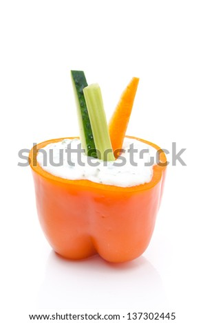 yoghurt sauce with herbs in half of orange pepper and assorted sliced �¢??�¢??fresh vegetables, isolated on white background