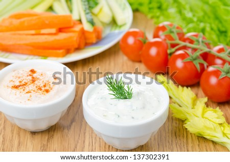 yoghurt sauce with herbs, sauce with sun-dried tomatoes and paprika to assorted fresh vegetables on a wooden table