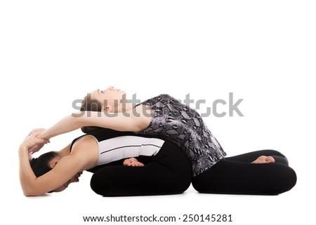 Yogi girls doing asana in pair, fitness training, stretching exercises, yoga practice with partner, sitting cross-legged, pose Padmasana, Lotus Position, isolated, white background - stock photo