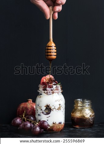 Yogurt and oat granola with grapes, pomegranate and grapefruit in a tall glass jar on black backdrop. Hand pours honey over the jar with a wooden stick - stock photo