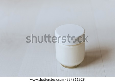 Yogurt in a glass jar on a white table.