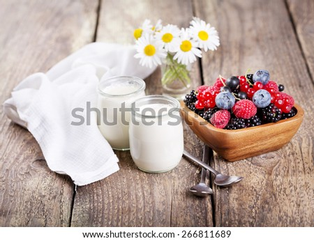 yogurt in a glass jars with fresh berries on wooden table - stock photo