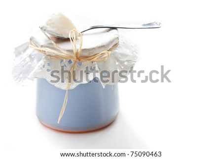 Yogurt in a small blue ceramic pot and spoon.