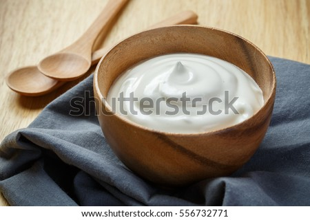 Yogurt in wooden bowl on wooden background with blue cotton and wooden spoon. plain yoghurt. yogurt. yoghurt.