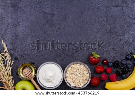 Yogurt, Oat Flakes, Fresh Apples, Honey and Summer Berries. View from above, top studio shot of fruits