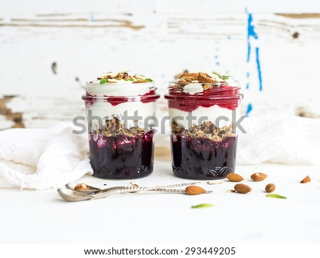 Yogurt oat granola with berries, honey and nuts in glass jars, rustic white backdrop - stock photo