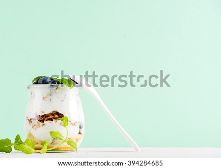 Yogurt oat granola with jam, blueberries and green leaves in glass jar on mint pastel backdrop, copy space - stock photo