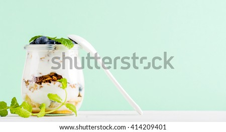 Yogurt oat granola with jam, blueberries and green leaves in glass jar on pastel mint backdrop, copy space - stock photo