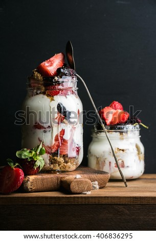 Yogurt oat granola with strawberries, mulberries, honey and mint leaves in tall and small glass jars on black backdrop, selective focus, copy space - stock photo