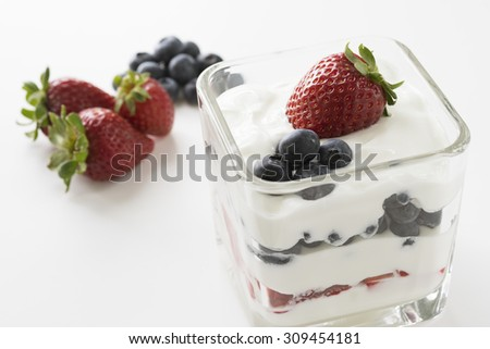 yogurt parfait with berries in the background