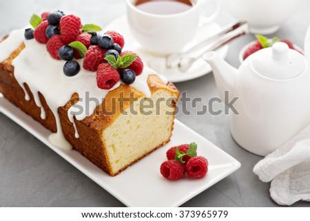 Yogurt pound cake for breakfast with glaze and fresh berries - stock photo
