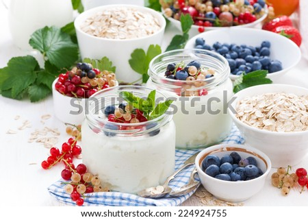 yogurt with berries and products for healthy breakfast, close-up - stock photo