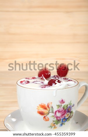 Yogurt with berries fresh raspberries. The berries fall in a bowl - stock photo