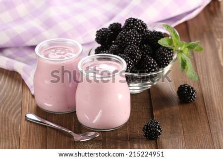 yogurt with blackberries in a glass jar and blackberries on the background of wooden boards