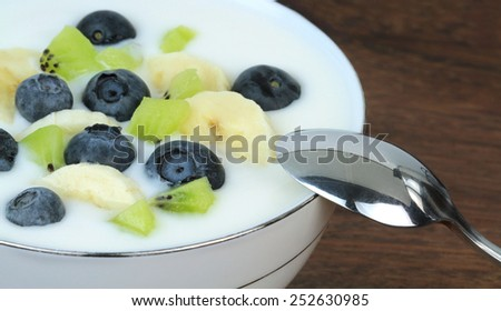 Yogurt with blueberries, kiwi and banana slices. - stock photo