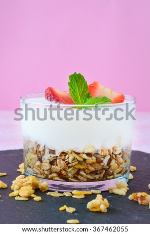 Yogurt with cereals and strawberries. Pink background