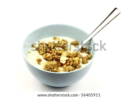 yogurt with crunchy breakfast cereals with all sorts of nuts in a blue bowl with a spoon - stock photo