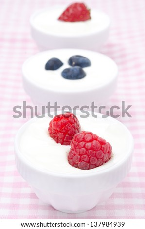 yogurt with different berries in bowls (with strawberries, blueberries, raspberries) close-up, vertical