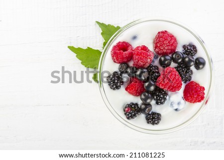 Yogurt with forest berries in bowl on white wooden table - stock photo