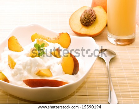 Yogurt with fresh peaches and mint for healthy breakfast. Light toning. - stock photo