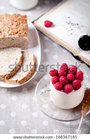 Yogurt with fresh raspberries in a glass cup with cane sugar crystals, brown bread, tea and book