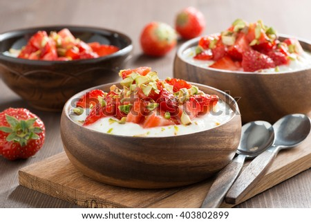 yogurt with fresh strawberries and pistachios in a bowls, close-up - stock photo