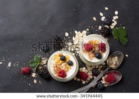 Yogurt with granola or muesli and fresh berries for healthy morning meal, selective focus - stock photo