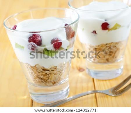 yogurt with muesli and berries in small glass - stock photo