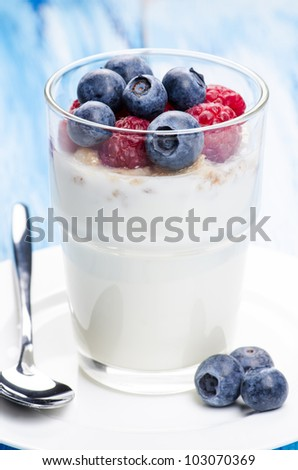Yogurt with raspberries and blueberries in a glass - stock photo