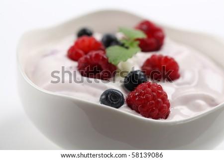 Yogurt with raspberries and blueberries. Shallow DOF - stock photo