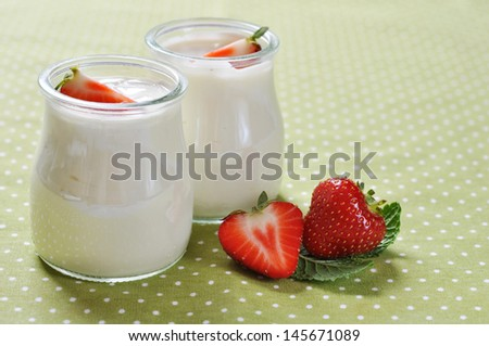 yogurt with ripe fresh strawberry in jars on green background