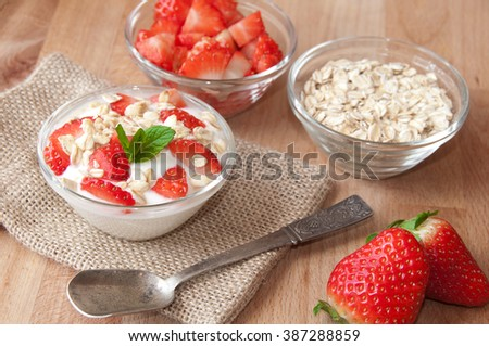 Yogurt with strawberries and cereals on wooden table
