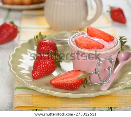 Yogurt with strawberries on a white background - stock photo
