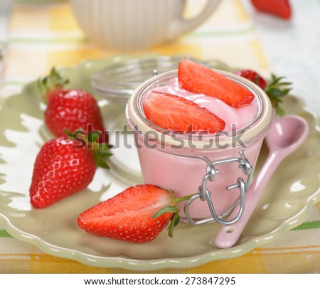 Yogurt with strawberries on a white background