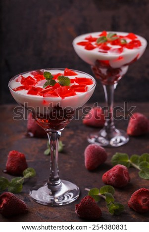 Yogurt with strawberry jelly in a glass glass, on a dark background.selective focus - stock photo