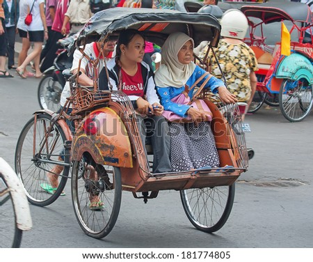 YOGYAKARTA, INDONESIA - AUGUST 03: Traditional rikshaw transport on streets of Yogyakarta, Java, Indonesia on August 03, 2010. Bicycle rikshaw remains popular means of transport in many Indonesian cities. - stock photo