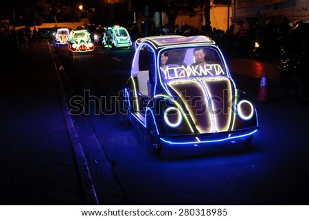 YOGYAKARTA, INDONESIA - JUNE 25, 2014: Undefined residents and tourists having fun riding on the illuminated pedal toy cars at night in Yogyakarta, Indonesia on June 25, 2014