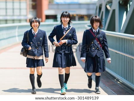 YOKOHAMA CITY, JAPAN - 07 MAY 2013: Three school girls walking along the bridge. Yokohama City, Japan. - stock photo