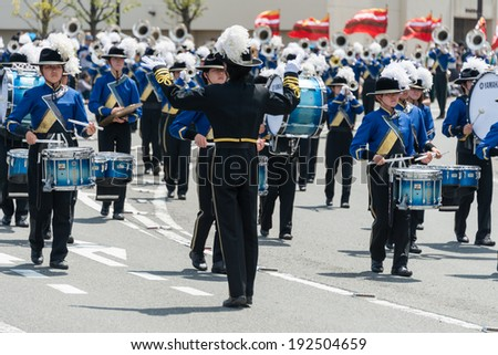 "YOKOHAMA, JAPAN - MAY 3, 2014: A marching band is on the street in ""The Yokohama Parade"". The parade marks the beginning of the ""Opening of the Port Festival""."