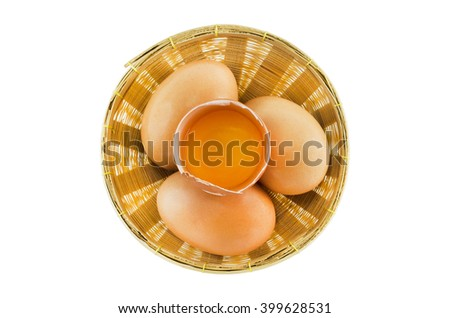 Yolk on the top of three fresh eggs in the wooden basket, isolated on white background