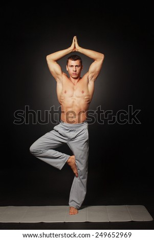 Yong  attractive athletic man doing a yoga pose isolated on black background  - stock photo