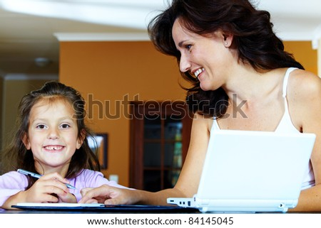 Yong brunette mother in her thirties helping her daughter with  homework while sitting at home behind computer - stock photo