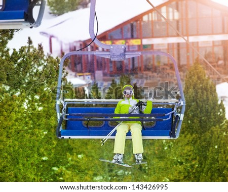 Yong happy woman sitting in ski lift chair and waiving her hand - stock photo