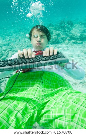 Yong man in formal clothes working with keyboard underwater - stock photo