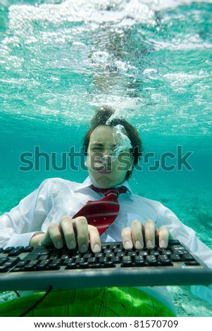 Yong man in formal clothes working with keyboard underwater with intense face expression - stock photo