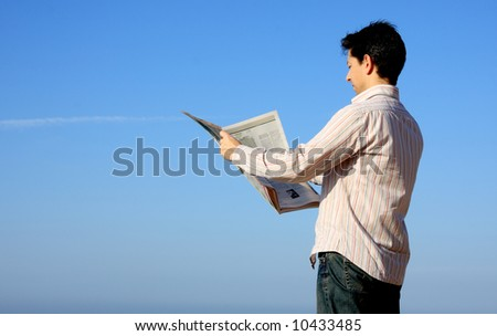 Yong man reading a newspaper with a blue sky on background - stock photo