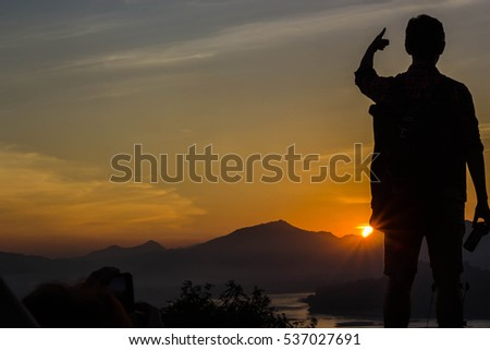Yong man standing on sunset backdrop