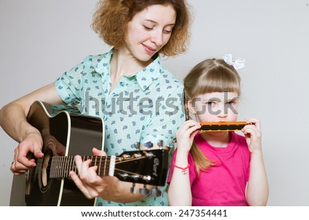 Yong mother and her  pretty daughter playing on  musical instruments, neutral background - stock photo