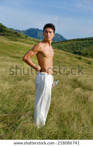 Yong muscular man in sport standing on mountain